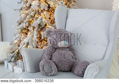 Teddy Bear Sitting On Grey Armchair By Glowing Lights Christmas Tree With Gifts. Scandinavian Decor