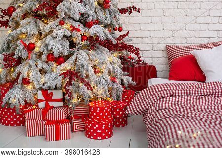 Christmas Gifts On The Floor Near Christmas Snow-covered Tree. New Year 2021. Cozy Decorated Bedroom
