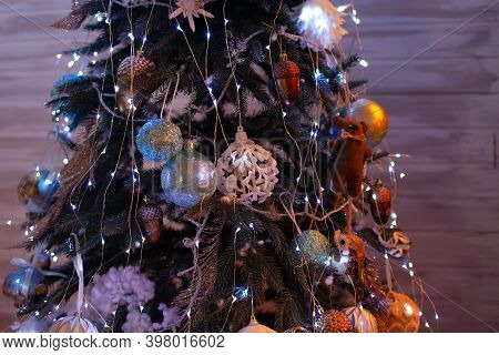 Glowing Christmas Tree In Dark At Night. Christmas Tree Decorated With Toys And Balls. Closeup View