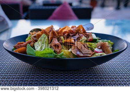 Fattoush (lebanese Salad) Close Up  Image In A Blue Plate . It Is Made With Vegetables And Crispy To
