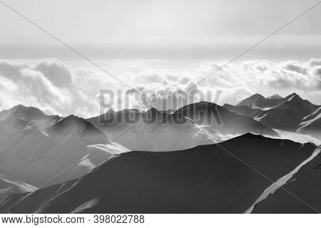 Silhouette Of Evening Sunlight Snowy Mountains In Mist. Caucasus Mountains, Georgia, Region Gudauri