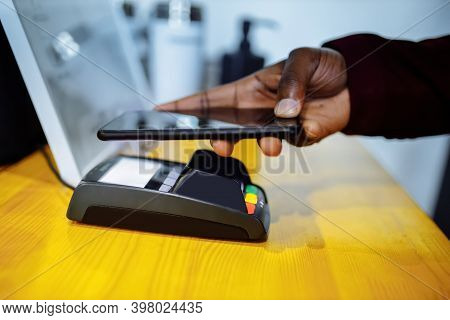 Close Up Hands Of African American Male Paying For Medical Insurance In Hospital Contactless Payment