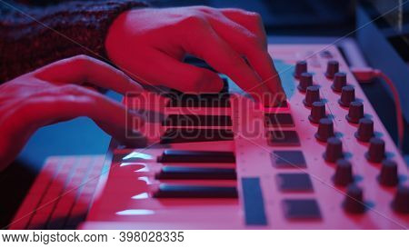 Closeup Of Hands Composing Music In Night Using Midi Controller. Playing Beat Music With Electronic