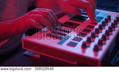 Male Hands Recording Music, Playing Electronic Keyboard, Midi Keys On The Table With Neon Lights. Cl
