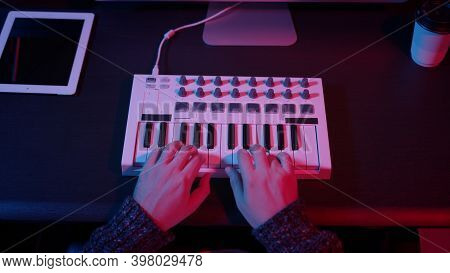 Closeup Of Hands Composing Music In Night Using Midi Controller. Top View Of Person Playing Music Wi
