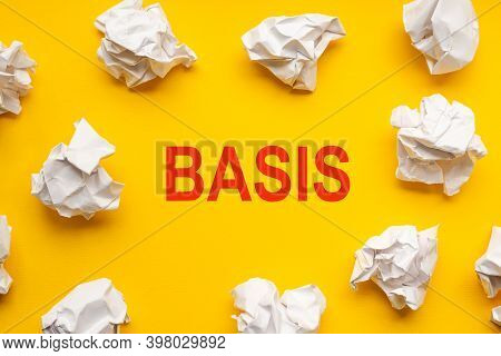 Basis Text On Yellow Background With Copy Space. Crumpled Sheets Of Paper Lie Around. Business Conce