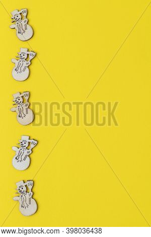 A Row Of Small Figures Of Wooden Snowmen On A Yellow Background