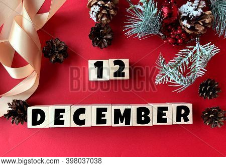 December 12 On Wooden Cubes.near Fir Branches, Cones, Ribbon, Gift Box On A Red Background.calendar