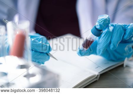 Technician Of Health With Blood Tubes In The Clinical Lab For Analytical , Hand Of Doctor Holding Bl