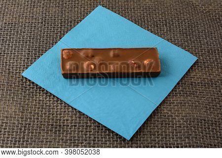 Hazelnut Milk Chocolate Candy Bar On Blue Napkin On Burlap