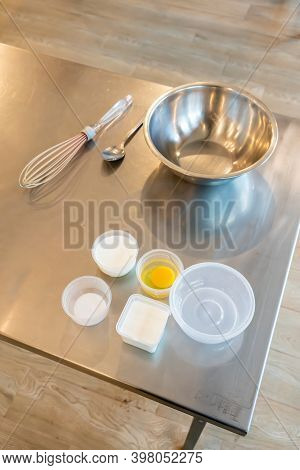 Prepared Ingredients For Making Homemade Ice Cream With Mixing Bowl And Whisker On Stainless Steel T