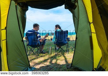 Happy Couple With Cups Of Tea At Camping By The Sea On Vacation