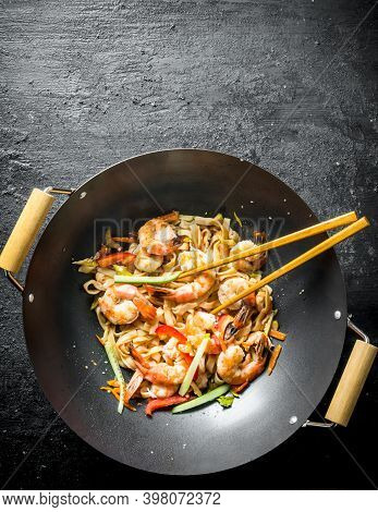 Fragrant Asian Udon Noodles In A Wok Pan. On Black Rustic Background