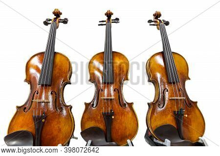 Three Classical Violins Isolated On A White Background. Musical Instruments Of The Symphony Orchestr