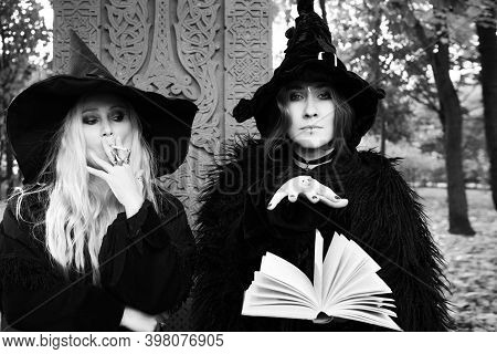 Two Witches On A Sabbath, A Witch In A Hat Reads A Spell From A Book. Halloween, Young Woman At The