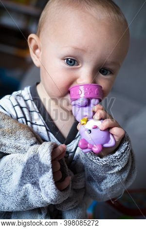 Baby Girl In Grey Clothes And Bathrobe Holds In Hands And Nibble A Violet Toy Cat. First Tooth. Clos