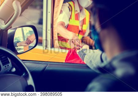 Selective Focus To Hand Of Driver Pay For The Expressway. Blurry Image Of Drivers And Cashiers Wear