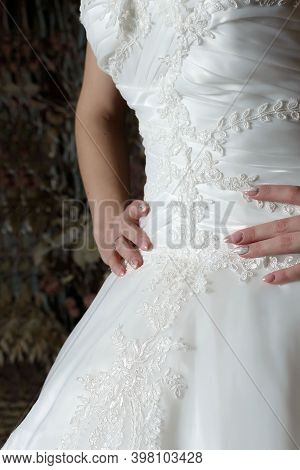 Close-up Bride's Dress With A Beautifully Embroidered Pattern And Hands On The Waist With A Beautifu