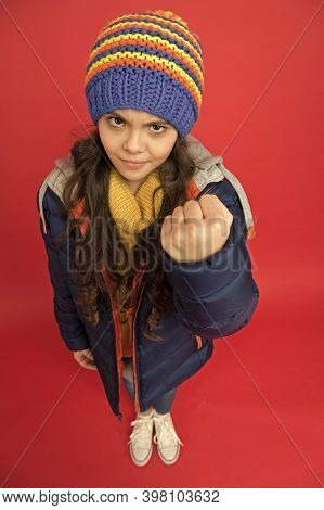 Punch In Face. Threatening Fist. Little Girl Wear Winter Clothes Red Background. Childhood Concept.