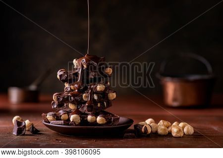Melted Chocolate Poured On Overlapping Pieces Of Dark Chocolate With Hazelnuts Still Life