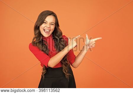 Look At This. Happy Kid Pointing At Brown Background. Little Child With Pointing Gesture. Index Fing