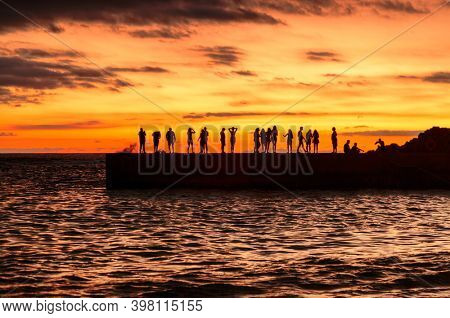 People silhouettes on the sea pier at sunset. Canary Tenerife island. Spain