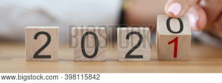 Numbers 2020 Make Up Wooden Cubes In Row. Female Hand Turn Number 2020 Into Number 2021 With Her Fin