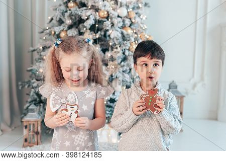 Boy And Girl Sit On Floor Under Christmas Tree. Children Eat Ginger Man. Waiting For Christmas. Cele