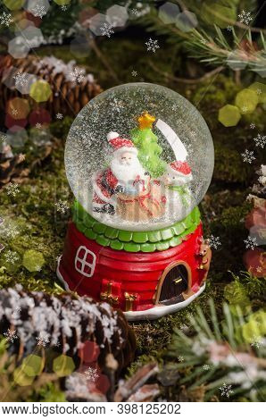 A Cute Christmas Toy, A Snow Globe With Santa Claus, A Snowman And A Christmas Tree Inside. Christma