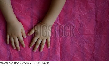 Toddler Hands On Crumpled Tissue Paper With Copy Space. Directly Above View Of Pink Wrinkled Paper A