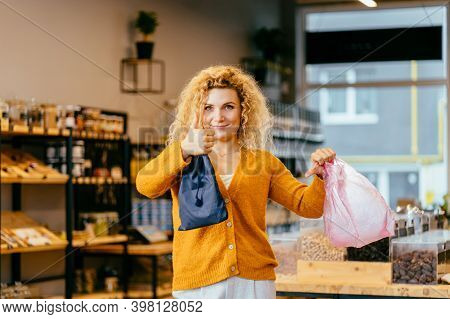 Blond Woman In Zero Waste Shop Or Plastic Free Store.female Holding Plastic And Reusable Cotton Bag