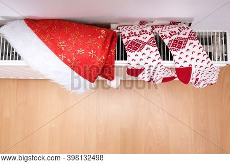 White And Red Christmas Socks And Santa Hat Hanging On Warm Central Heat Radiator, Winter Holiday Ho