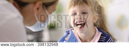 Woman Doctor Pediatrician In Protective Medical Mask And Rubber Gloves Examines Throat Of Little Gir