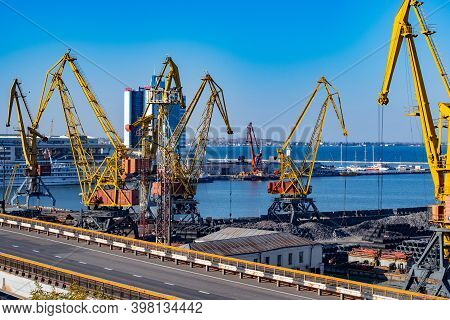 Modern Elevated Road And Seaport Industrial Landscape With Shore Cranes Jibs And Piles Of Bulk Cargo