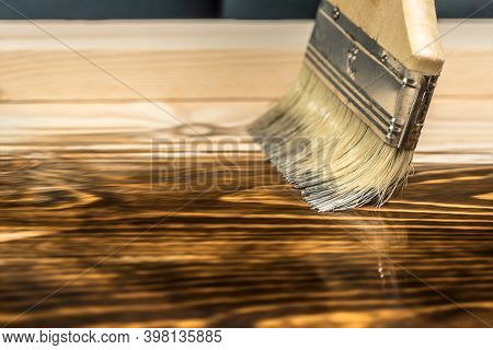 A Close-up Paint Brush That Paints A Wooden Table With Brown Stain Or Paint, With The Appearance Of