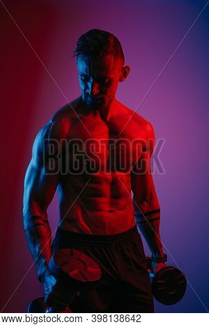 A Muscular Man With A Beard Who Is Doing Bicep Hammer Curls With Dumbbells Under Blue And Red Lights