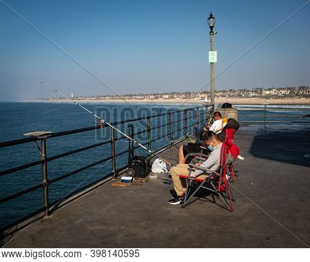 Huntington Beach, Ca, U.s.a. - Nov. 26, 2020: A Young Masked Man Sits In A Group Of Fishermen On The