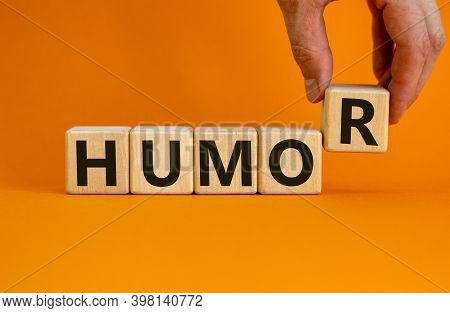 Humor Symbol. Wooden Cubes With Word 'humor'. Male Hand. Beautiful Orange Background. Business And H