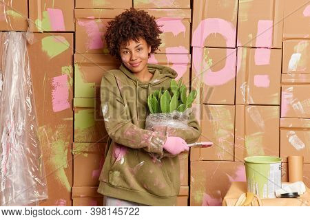 Satisfied Female Homeowner Holds Paint Brush And Potted Cactus Busy Doing Repair In New House Dresse