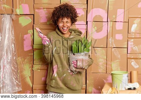 Overjoyed Female House Owner Has Fun While Refurbishing Walls Of House Holds Pot Of Cactus Paint Bru