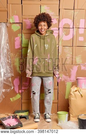 Vertical Shot Of Dark Skinned Woman Dressed In Casual Clothes Happy To Finish Refurbishment Of Walls