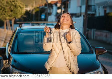 Happy Attractive Woman Holding A Key Of Her New Car. Successful Car Buying Or Rental.