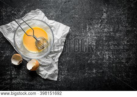 Beaten Egg In A Bowl With A Whisk On Paper.