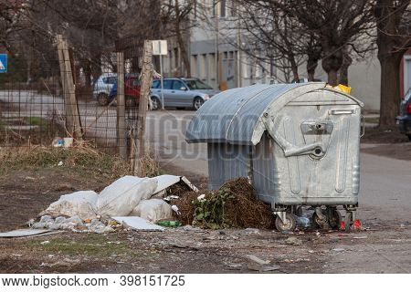 Garbage Bins And Containers Full, Overflowing, With Bags Falling On Ground In Residential Area Of Be