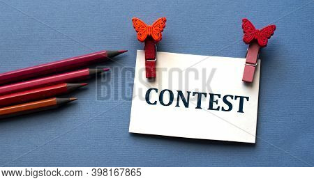 Contest - Word On White Cardboard With Beautiful Clothespins And Red Pencils. Concept Dreams