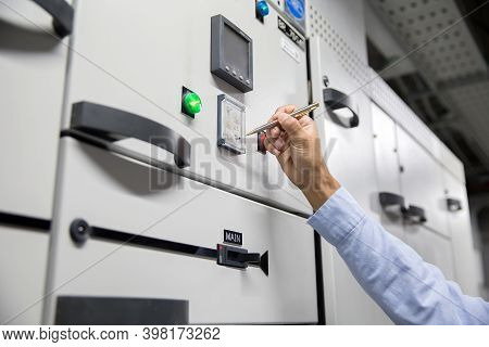 Close-up Hand Of Electrical Engineer Checking The Electric Current Voltage And Overload At Front Of