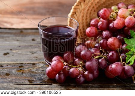 Fresh Red Grapes Fruit In A Basket And Juice On Wooden Background
