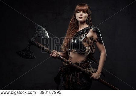 Armed With Huge Axe And Armoured Woman Viking With Long Brown Hairs Poses In Dark Background.