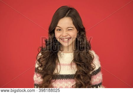 Winking Face. Natural Curls. Kid Cute Face Adorable Curly Hairstyle. Kid Girl Long Hair Posing Confi