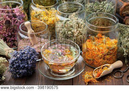 Cup Of Healthy Calendula Tea, Jars Of Dry Medicinal Herbs - Heather, Calendula, Coneflowers, Melissa